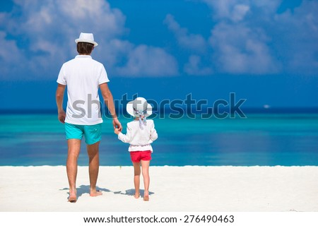Adorable little girl and dad during tropical beach vacation - stock photo