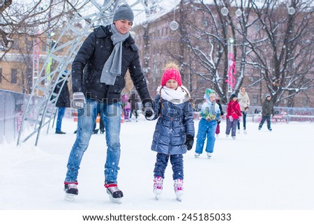Adorable little girl and happy dad on skating rink outdoor - stock photo