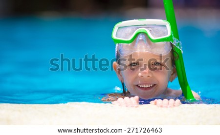 Adorable little girl at mask and goggles in outdoor swimming pool - stock photo