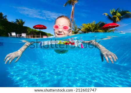 Adorable little girl at swimming pool - stock photo