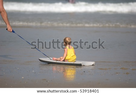 Adorable little girl being pulled by her dad on the boogie board - stock photo