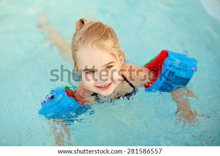 Adorable little girl blonde swimming in the pool with armbands and laughs - stock photo