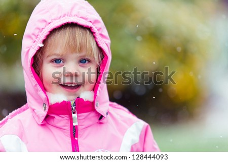 adorable little girl bundled up int the snow - stock photo