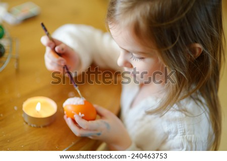 Adorable little girl coloring an Easter egg using wax and dyes - stock photo