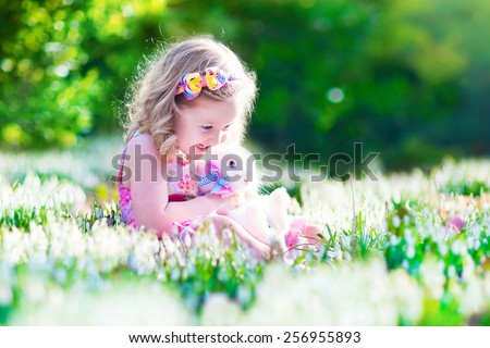 Adorable little girl, cute curly toddler in a colorful summer dress, playing with a real rabbit, having fun with her pet bunny in a beautiful garden with first spring snowdrop flowers - stock photo