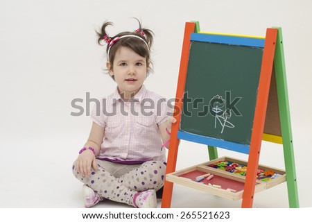 Adorable little girl draw two flowers on black board with chalk isolated on white background - stock photo