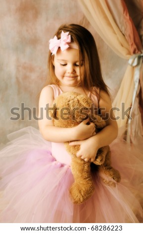 Adorable little girl dressed as a ballerina in a tutu, hugging a teddy bear next to pink roses. - stock photo