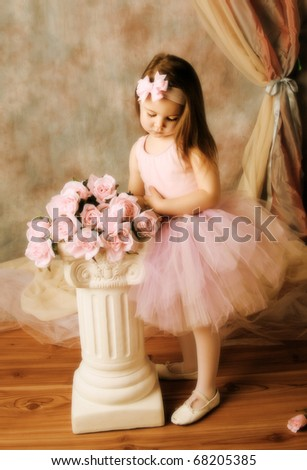 Adorable little girl dressed as a ballerina in a tutu standing next to pink roses. - stock photo