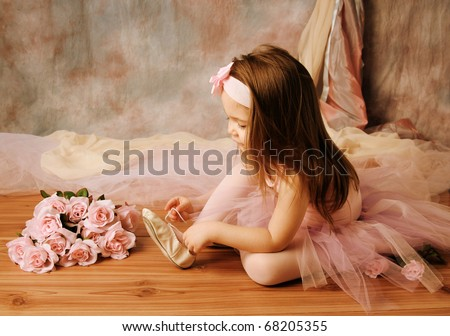 Adorable little girl dressed as a ballerina in a tutu, tying her ballet slippers - stock photo