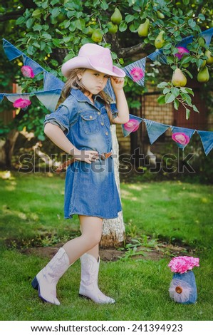 Adorable little girl dressed as a cowgirl outdoors - stock photo
