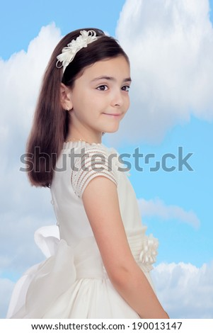Adorable little girl dressed in communion with a blue sky of background - stock photo