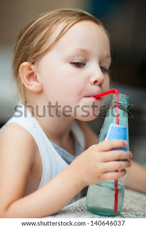 Adorable little girl drinking water from a bottle using a straw - stock photo