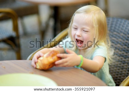Adorable little girl eating a bun in an outdoor cafe on warm summer day - stock photo