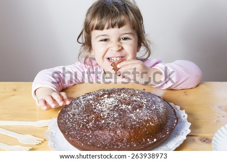 Adorable little girl eating a homemade chocolate cake. Very funny  and play toddler taking a piece of  delicious cake - stock photo