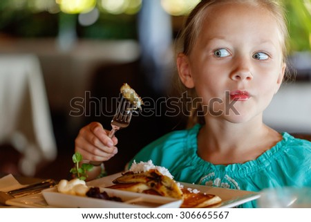 Adorable little girl eating breakfast in restaurant - stock photo