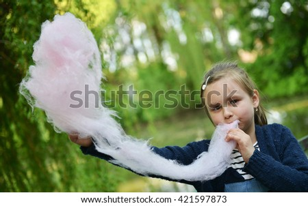 Adorable little girl eating candy-floss - stock photo