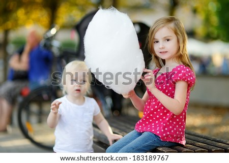 Adorable little girl eating candy-floss outdoors at summer - stock photo