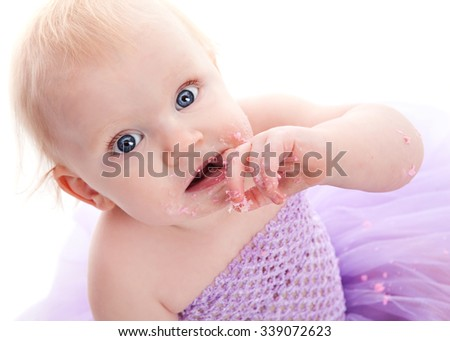 Adorable little girl eating her birthday cake and looking up at the camera.  Isolated on white.   - stock photo