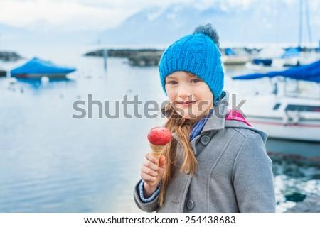 Adorable little girl eating ice cream outdoors - stock photo