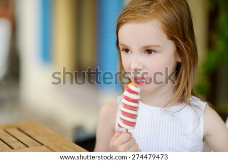 Adorable little girl eating ice-cream outdoors - stock photo