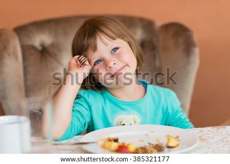 Adorable little girl eating pancake for a breakfast in restaurant - stock photo