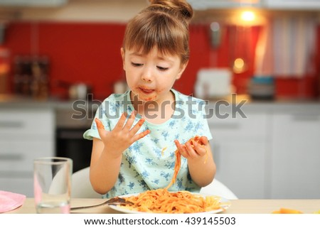 Adorable little girl eating spaghetti at table - stock photo