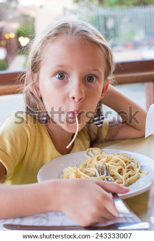 Adorable little girl eating spaghetti in outdoors restaraunt - stock photo