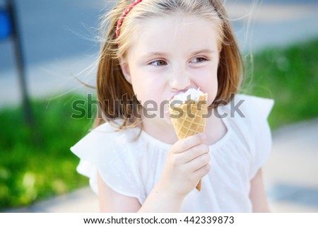 Adorable little girl eating tasty ice cream at park on warm sunny summer day - stock photo