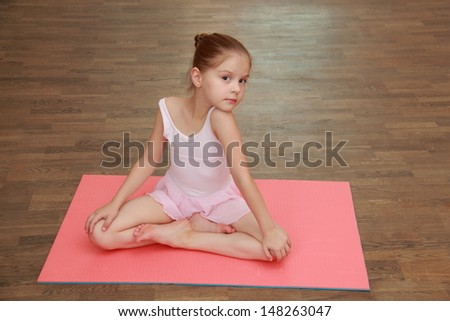 Adorable little girl engaged in a pink ballet tutu and pointe in the ballet hall on the wooden dance floor - stock photo