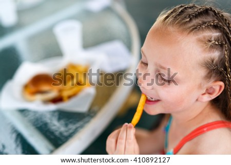 Adorable little girl enjoying eating french fries at outdoors restaurant on summer day - stock photo