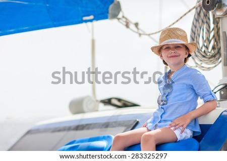 Adorable little girl enjoying sailing on a luxury catamaran or yacht - stock photo