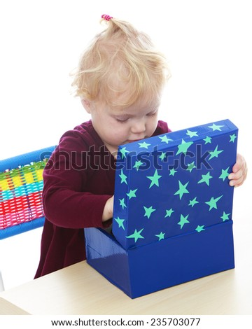 Adorable little girl enthusiastically looks into the big blue box sitting at the table .White background, isolated photo. - stock photo