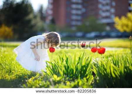 Adorable little girl girl smelling a tulip at summer - stock photo