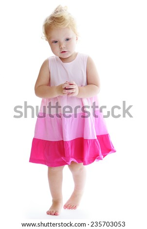Adorable little girl goes barefoot on the floor.White background, isolated photo. - stock photo