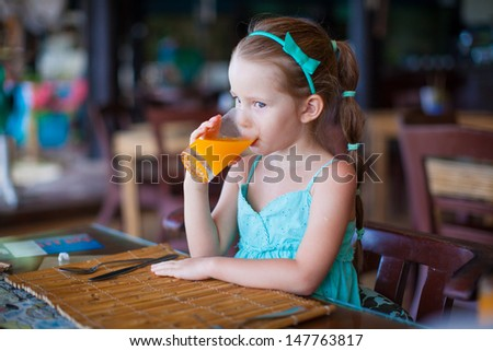 Adorable little girl having breakfast and drinking juice at resort restaurant - stock photo
