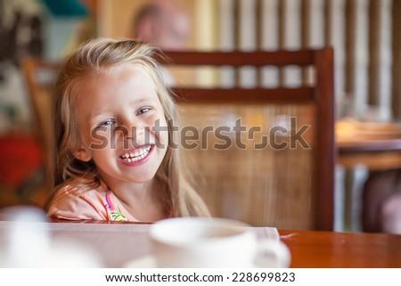Adorable little girl having breakfast at resort restaurant outdoors - stock photo