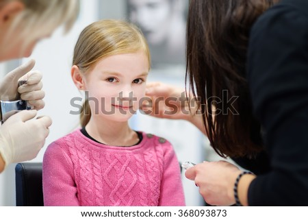 Adorable little girl having ear piercing process with special equipment in beauty center by medical worker - stock photo