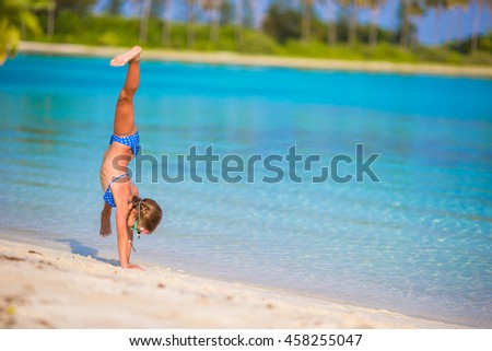Adorable little girl having fun at beach during summer vacation - stock photo
