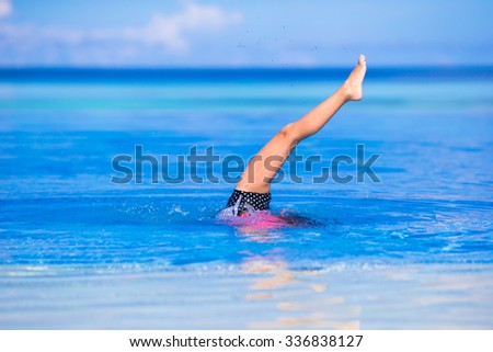 Adorable little girl having fun in outdoor swimming pool - stock photo