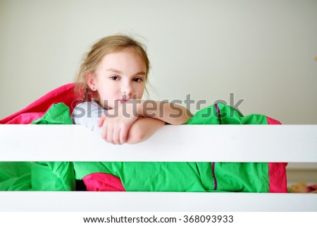 Adorable little girl having fun in twin bunk bed on sunny sunday morning - stock photo