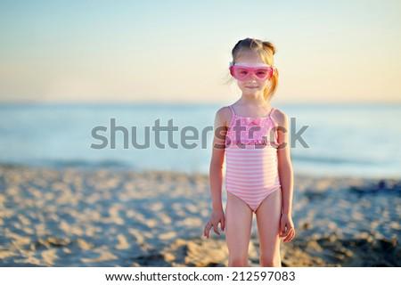 Adorable little girl having fun on a beach on summer evening - stock photo