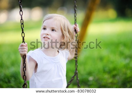 Adorable little girl having fun on a swing - stock photo