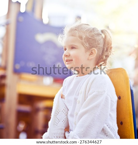 Adorable little girl having fun on a swing outdoors closeup - stock photo