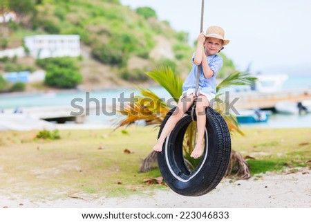 Adorable little girl having fun on tire swing on summer day - stock photo