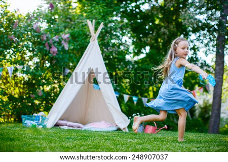 Adorable little girl having fun playing outdoors on summer day - stock photo