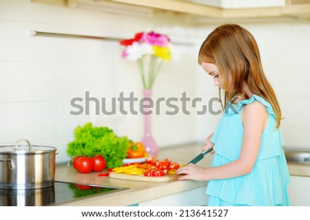 Adorable little girl helping her mother to cook dinner in a kitchen - stock photo