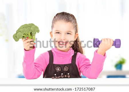 Adorable little girl holding broccoli and a dumbbell, seated at table - stock photo