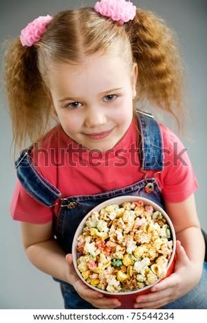 Adorable little girl holding large popcorn bucket - stock photo