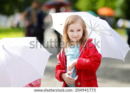 Adorable little girl holding white umbrella at rainy day in autumn - stock photo