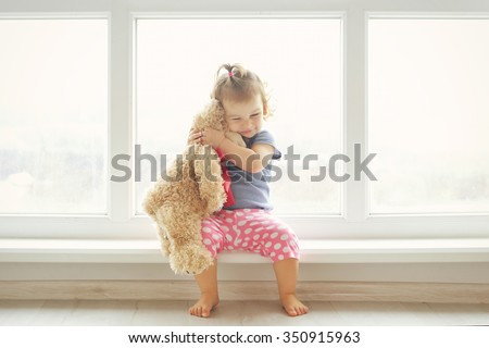 Adorable little girl hugging a teddy bear. Cute baby at home in white room is sitting near window.  - stock photo